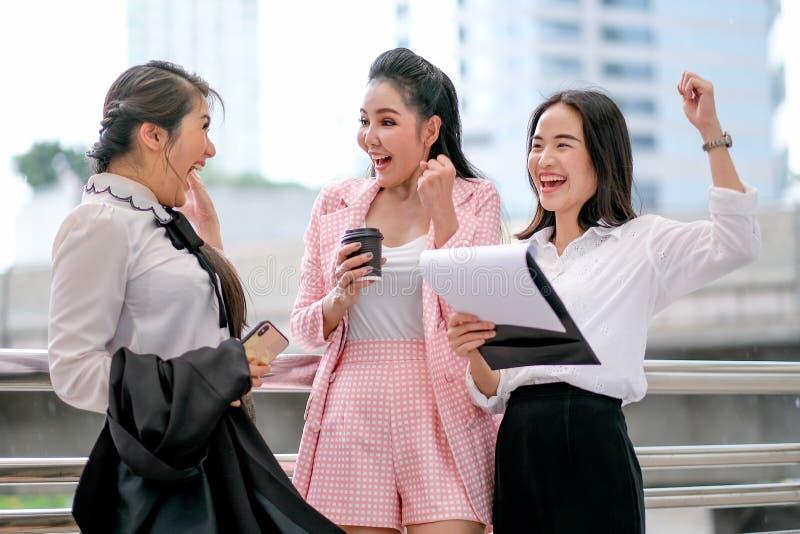 在白天,三个企业亚裔女孩作为愉快并且令人激动在办公室外 免版税库存照片