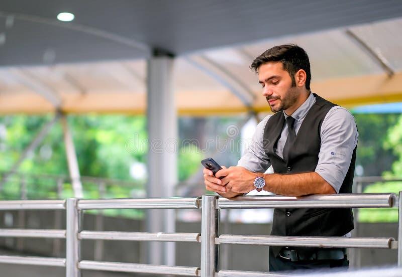 在白天,白种人白色商人在天空火车步行方式的看看他的手机和立场,也表现出哀伤的情感 免版税库存照片
