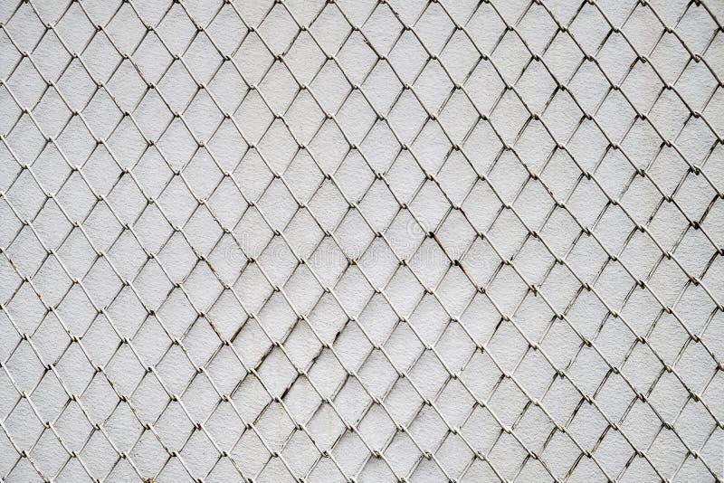 在白水泥墙壁背景的链节篱芭 免版税库存图片
