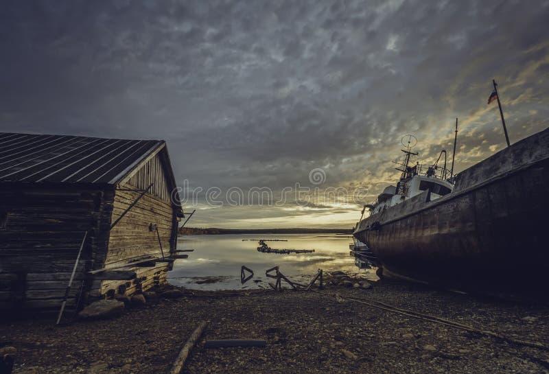 在白海的美好的日落有船和老房子的 图库摄影