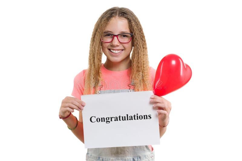 在白皮书写的祝贺短信在手相当青少年女孩,有红心气球的微笑的女孩  免版税库存照片