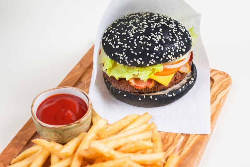 在白皮书的黑汉堡用炸薯条和一个杯子用西红柿酱在一个木板 库存图片