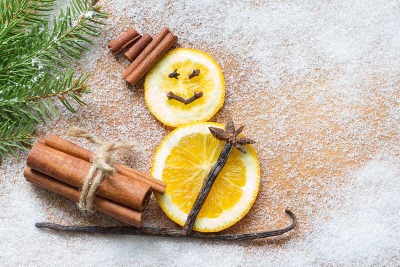 在白糖背景的圣诞节装饰品橙色抽象雪人 免版税库存照片