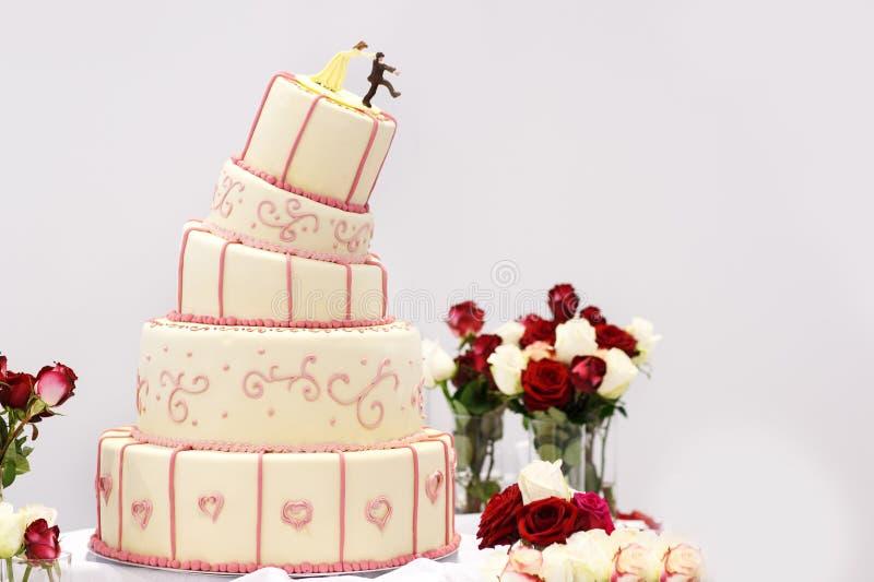 在白色、奶油和桃红色的可口婚宴喜饼 免版税库存照片
