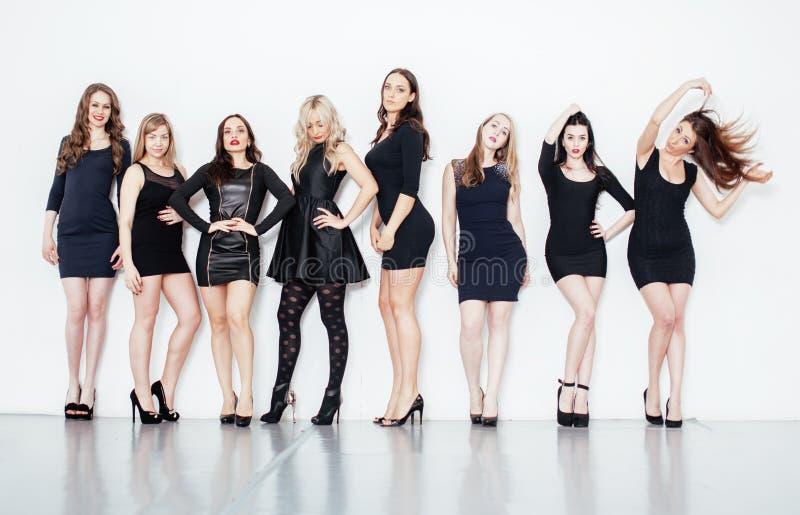在白色不同的时尚样式黑色礼服的许多凉快的现代女朋友一起获得乐趣隔绝的小组  库存照片
