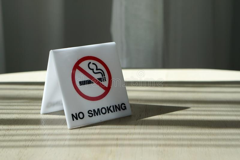 在白色丙烯酸酯的普通禁烟标志在木材桌上 免版税库存图片