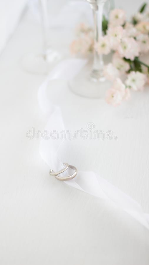 在白色丝带的两结婚戒指 花和champane玻璃轻的迷离背景  库存图片