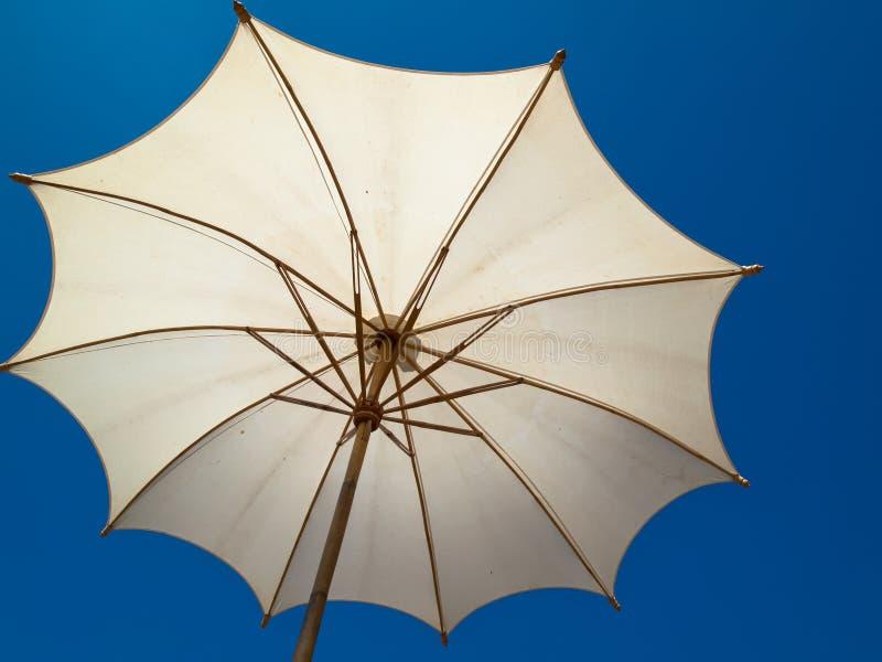 在白色之下的竹伞 免版税库存图片