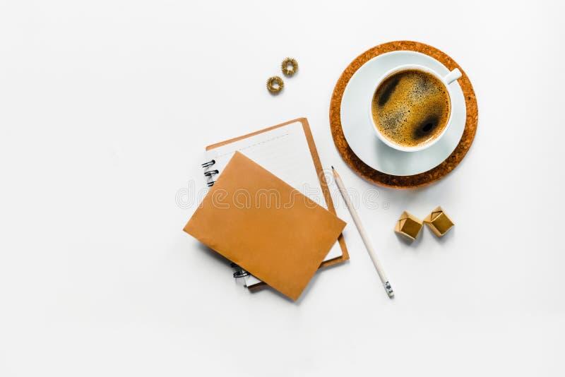 在白色书桌上的鲜美芳香咖啡有纸的 免版税图库摄影