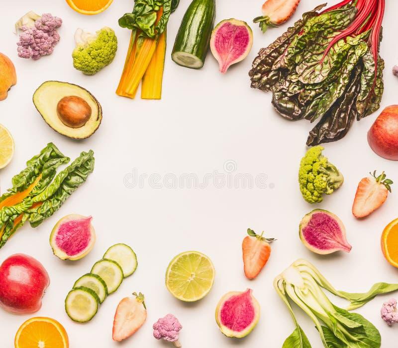 在白色书桌背景,顶视图,平的位置的各种各样的健康水果和蔬菜成份框架 免版税库存图片