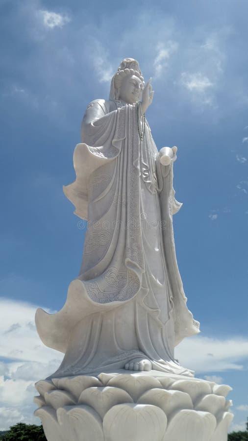 在白色云彩和蓝天围拢的莲花白色大理石雕塑的大母亲女神观世音菩萨立场 免版税库存照片