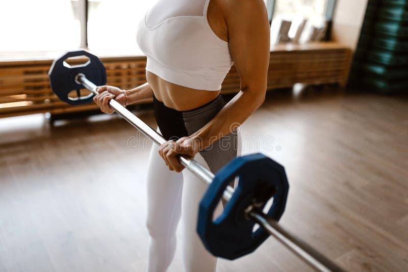 在白色体育上面和贴身衬衣打扮的运动女孩举在健身房的杠铃 免版税图库摄影