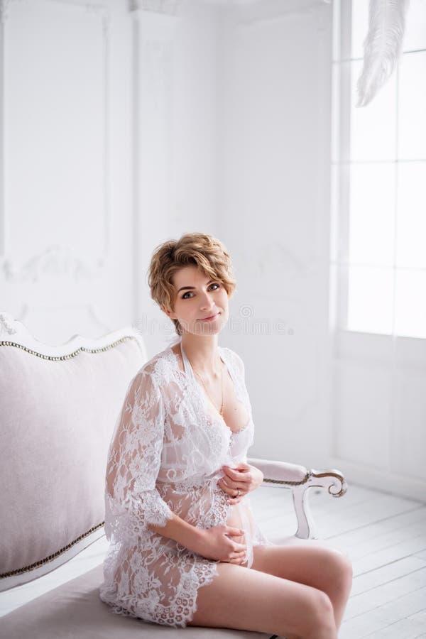 在白色内部的年轻人孕妇佩带的鞋带礼服 方式射击 免版税库存照片