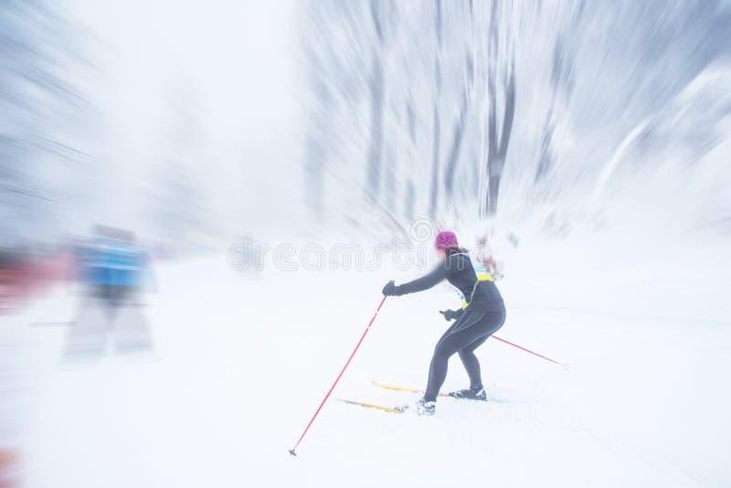 在白色冬天自然的女性北欧滑雪者乘驾 免版税库存图片