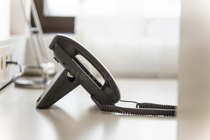 在白色办公桌上的黑输送路线电话 免版税库存照片