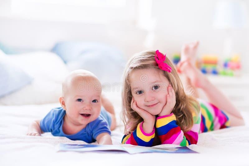 读在白色卧室的孩子 免版税库存照片