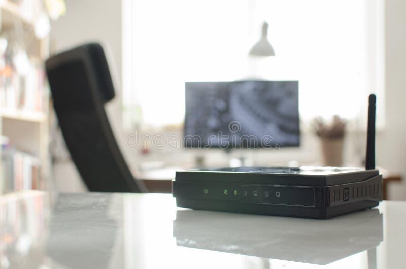 在白色反射性桌上的黑无线路由器 图库摄影