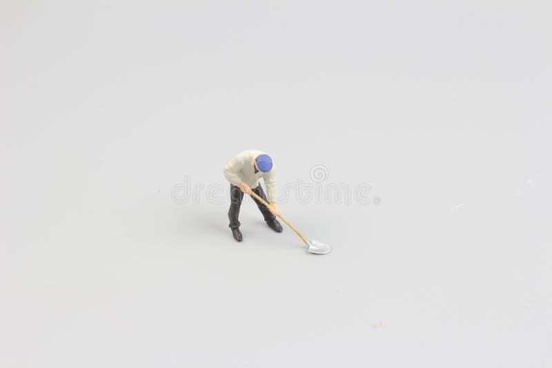 在白色后面地面的微型工作者孤立 免版税库存图片