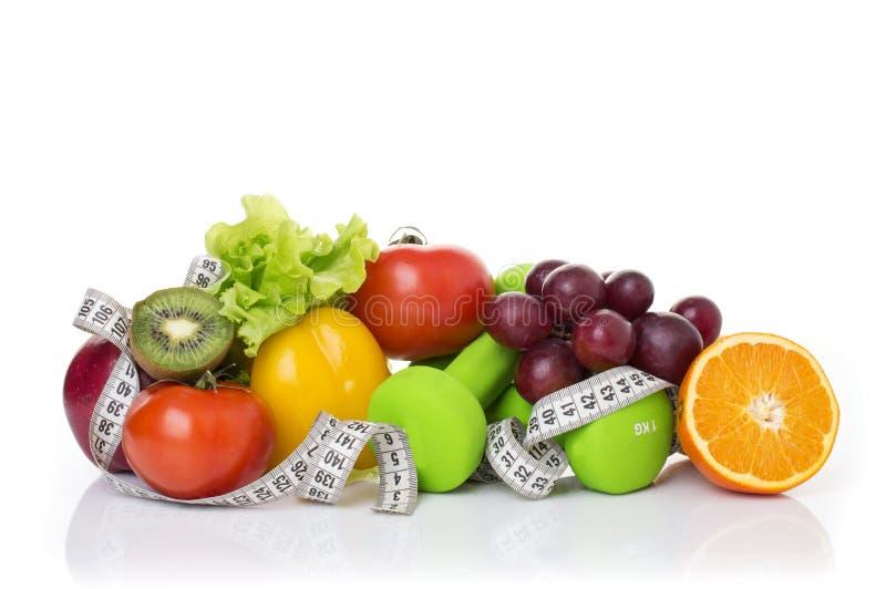 在白色和健康食品隔绝的健身设备 苹果、胡椒、葡萄、猕猴桃、桔子、哑铃和测量的磁带 库存图片