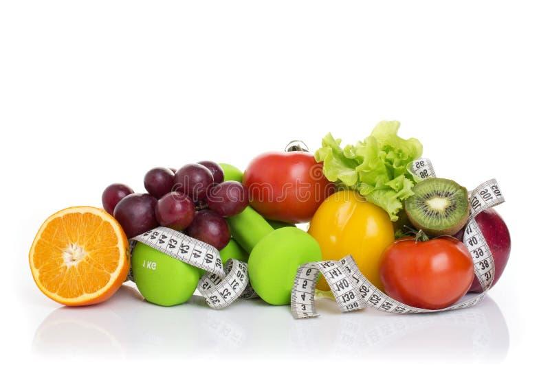 在白色和健康食品隔绝的健身设备 苹果、胡椒、葡萄、猕猴桃、桔子、哑铃和测量的磁带 免版税库存图片