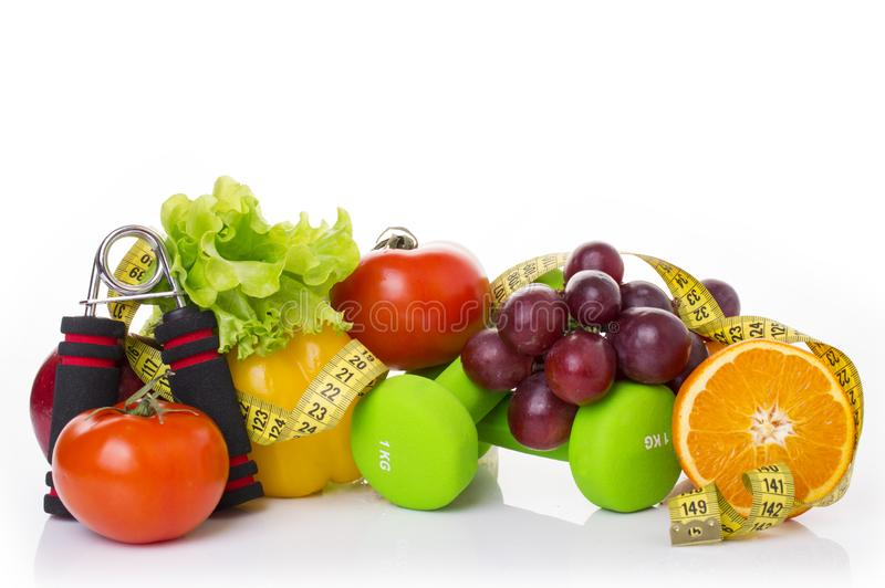 在白色和健康食物隔绝的健身设备 苹果、胡椒、葡萄、猕猴桃、桔子、哑铃和测量的磁带 免版税库存照片