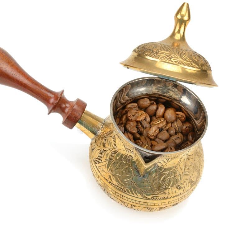 在白色和咖啡豆隔绝的咖啡壶 图库摄影
