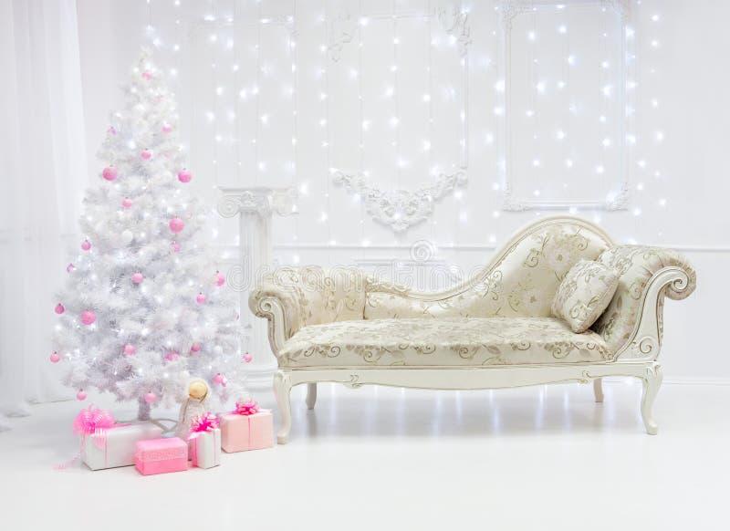 在白色和桃红色口气的经典圣诞灯内部与长沙发 免版税图库摄影