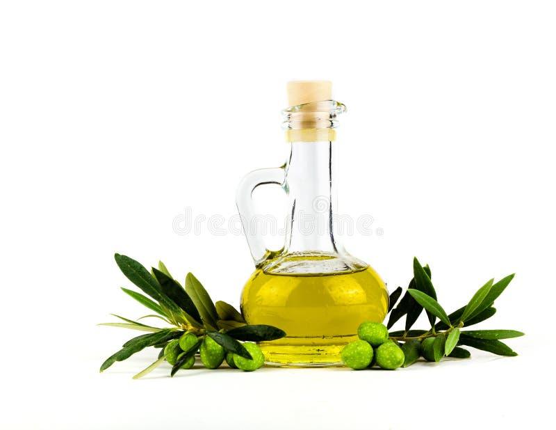 在白色和橄榄树枝隔绝的橄榄油瓶 免版税库存照片
