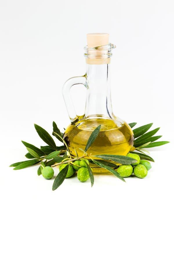 在白色和橄榄树枝隔绝的橄榄油瓶 库存图片