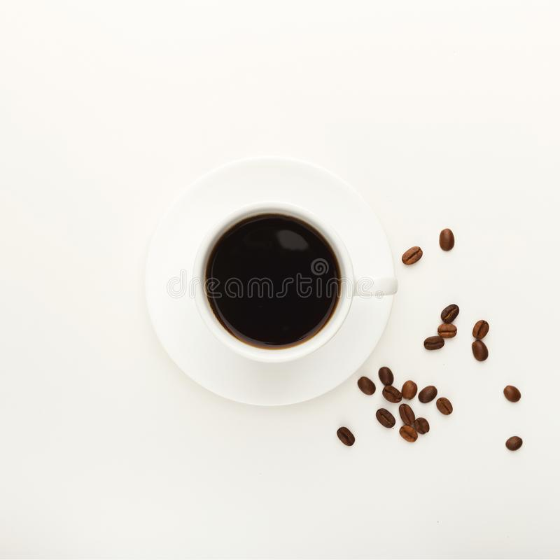 在白色和烤豆隔绝的无奶咖啡杯子 图库摄影