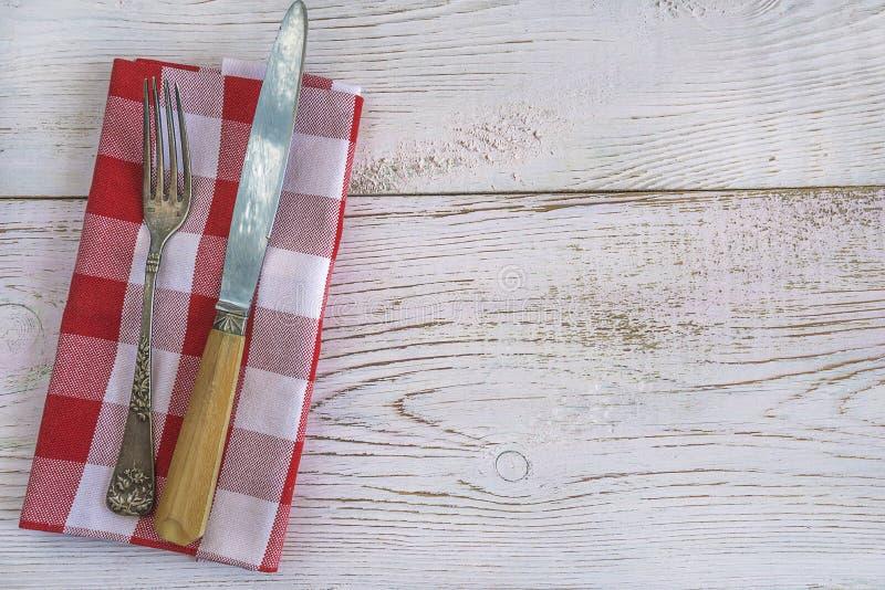 在白色和红色方格的餐巾的葡萄酒利器 库存图片