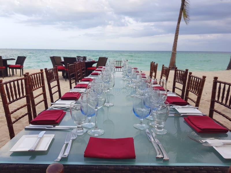 在白色和红色的美好的桌设置在海滩旁边在巴哈马 蓝色水晶酒杯和红色餐巾 免版税库存照片