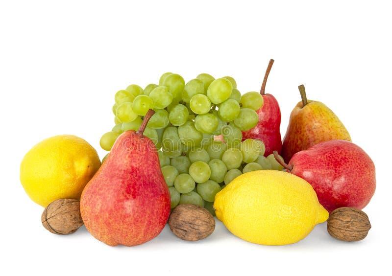 在白色和红色芬芳梨柠檬隔绝的果子盛肉盘成熟黄色柠檬、绿色葡萄、核桃 免版税库存图片