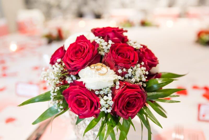 在白色和英国兰开斯特家族族徽新娘花束的婚戒 免版税图库摄影