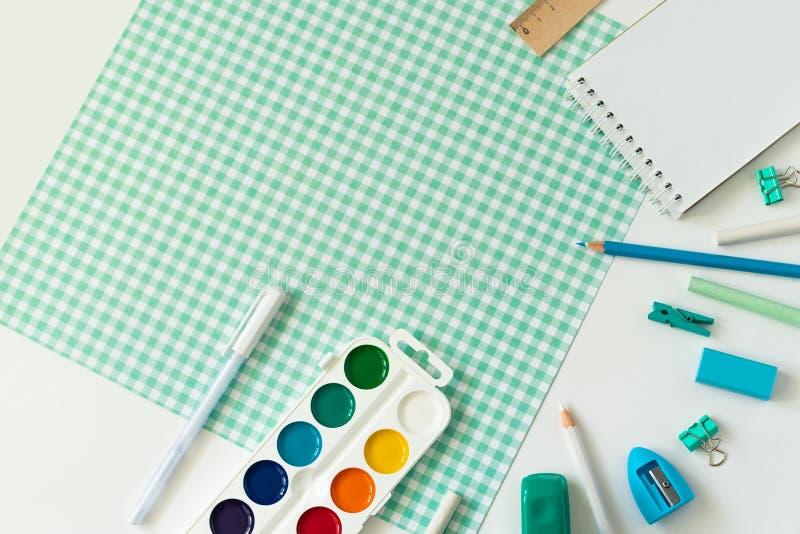 在白色和蓝色方格的背景的学校用品 库存照片