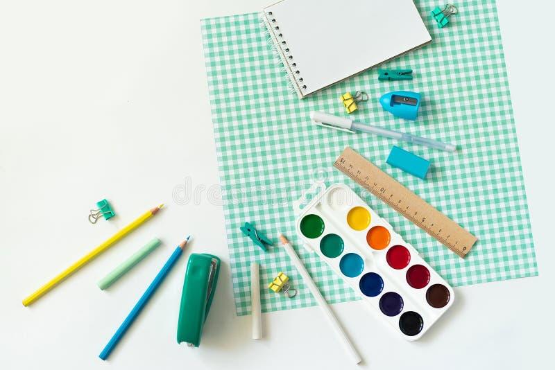 在白色和蓝色方格的背景的学校用品 免版税库存图片