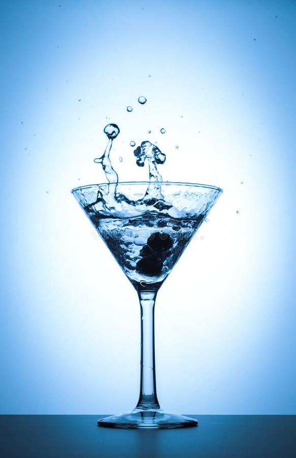 在白色和蓝色梯度背景的鸡尾酒马蒂尼鸡尾酒玻璃飞溅 免版税库存图片