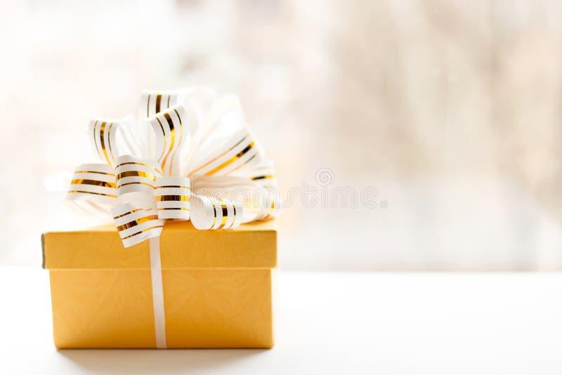 在白色和金子包裹的黄色礼物盒镶边了在轻的背景的丝带 被栓的空的笔记  复制空间 安置文本 免版税库存照片
