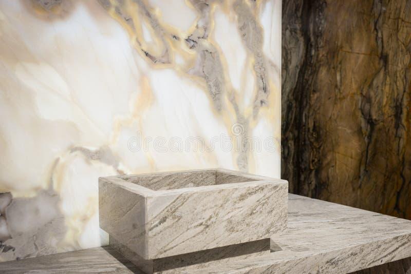 在白色和黑暗的大理石墙壁附近的方形的水盆 免版税库存图片