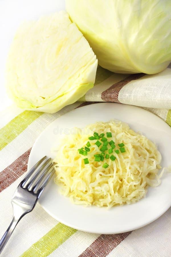 在白色圆白菜白色板材和头的德国泡菜  图库摄影