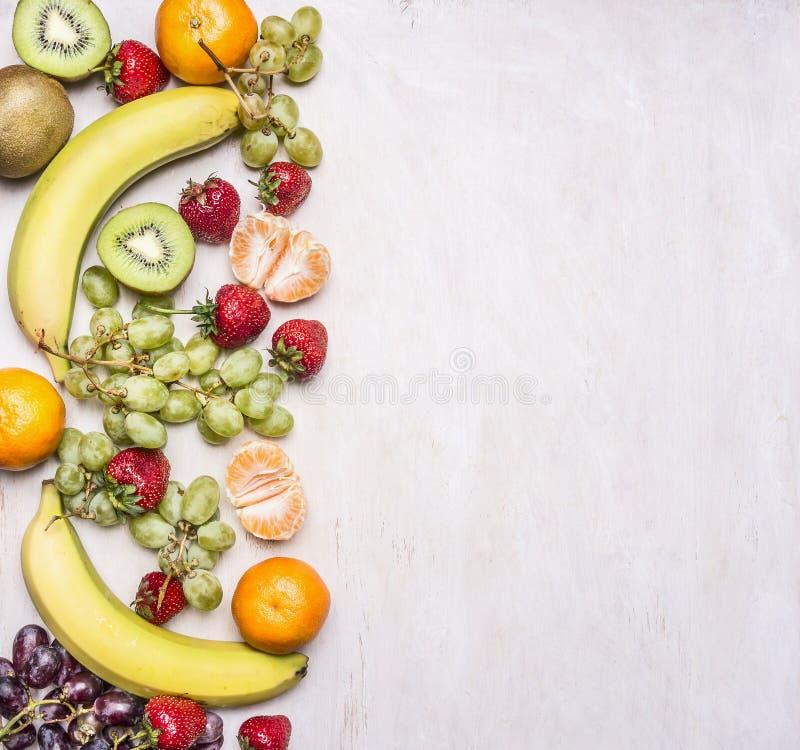 在白色土气背景顶视图Superfoods健康的一个边界计划的新鲜水果的可口分类或戒毒所死 库存照片