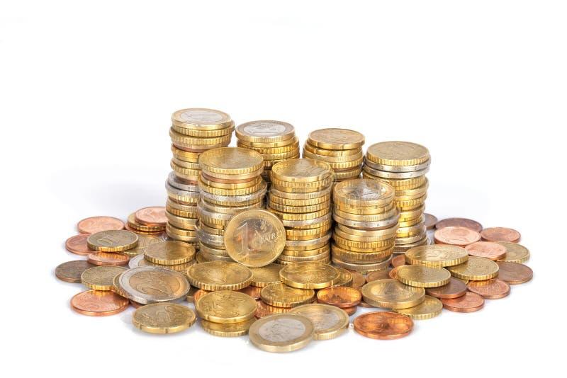在白色堆积在专栏和隔绝的堆欧洲硬币 库存照片