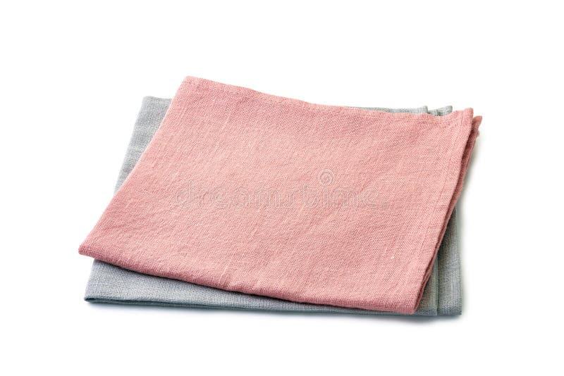 在白色堆积的被折叠的淡粉红和苍白灰色餐巾 免版税图库摄影
