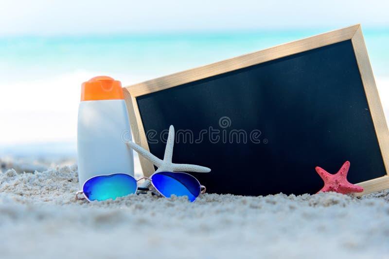 在白色塑料瓶的防护遮光剂或sunblock和sunbath化妆水有在热带海滩的凉鞋的 chalkbo的特写镜头 免版税图库摄影