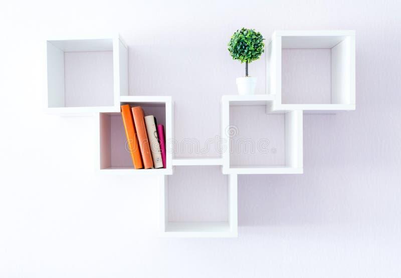 在白色墙壁上的一个现代白色书架有若干事件和花的 简单派样式 免版税库存图片