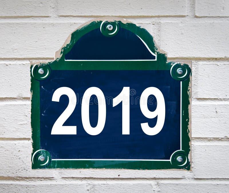 在白色墙壁上的一块巴黎街道板材写的2019年 免版税库存照片