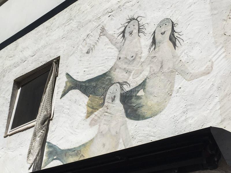 在白色墙壁上的三个美人鱼 免版税图库摄影