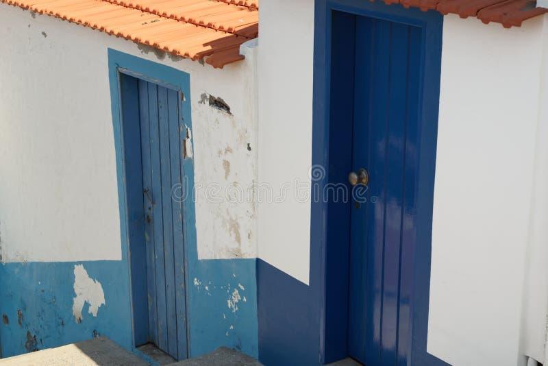 在白色墙壁上的两个蓝色门 免版税库存照片