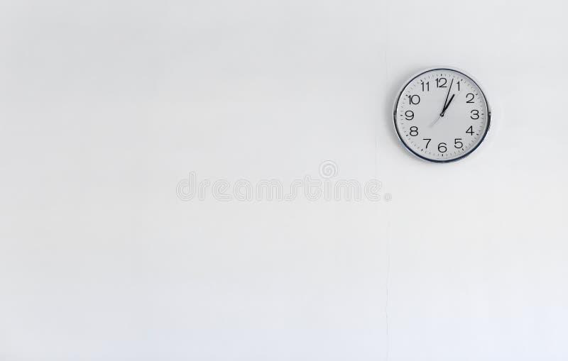 在白色墙壁上的圆的金属时钟 库存照片