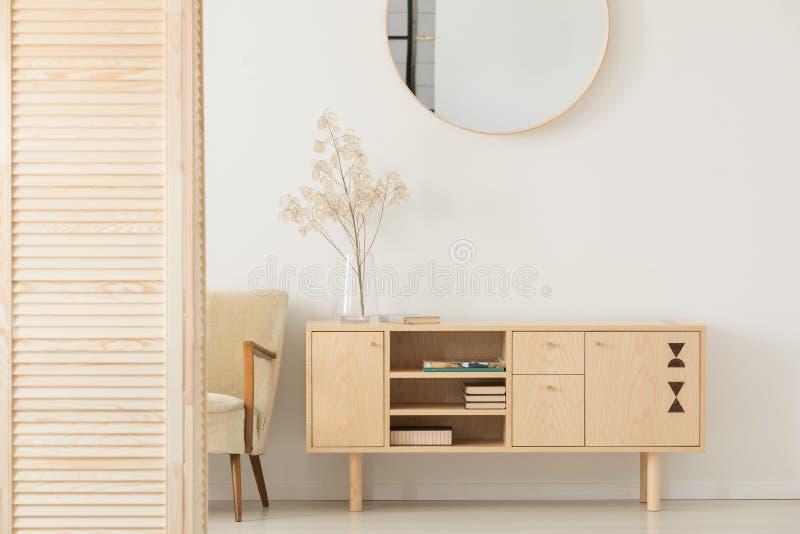 在白色墙壁上的圆的镜子在简单的前室的木内阁上内部与扶手椅子 免版税库存照片